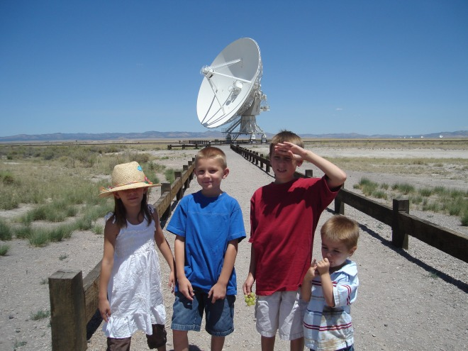 the kids in front of an parabolic dish